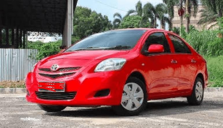 gambar ini menunjukkan mobil bekas taksi dengan warna merah tampak depan