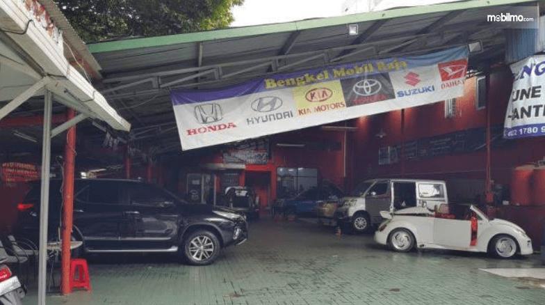 Gambar ini menunjukkan bengkel mobil dengan beberapa mobil di dalamnya