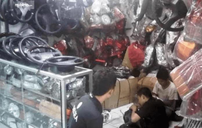 Gambar ini menunjukkan toko sparepart mobil dan ada beberapa orang