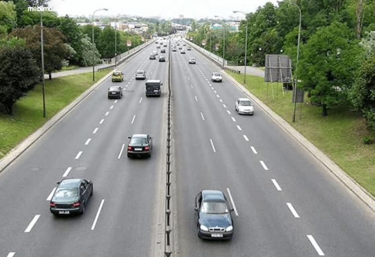 Gambar ini menunjukkan beberapa mobil melaju di jalan yang dengan 2 jalur berbeda