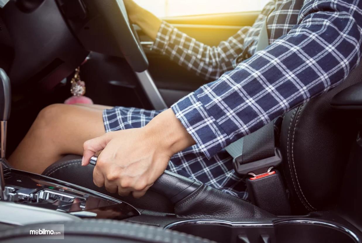 Foto seorang pengemudi bersiap menonaktifkan rem tangan
