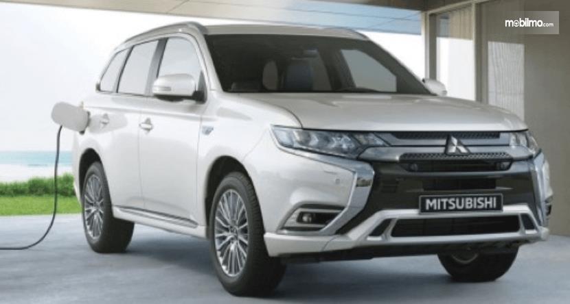 hambar ini menunjukkan Mitsubishi OUTLANDER PHEV putih tampak depan dan samping kanan