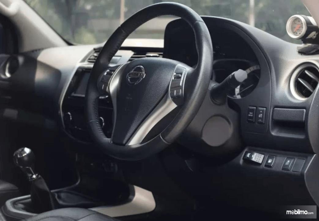 Gambar ini menunjukikan bagian dashboard dan kemudi mobil Nissan Navara 2015