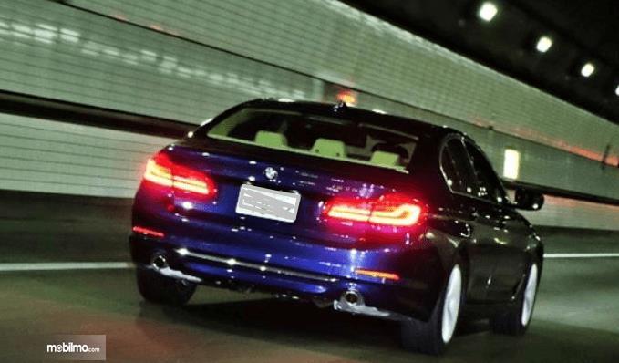 Gambar ini menunjukkan mobil melaju di malam hari tampak belakang