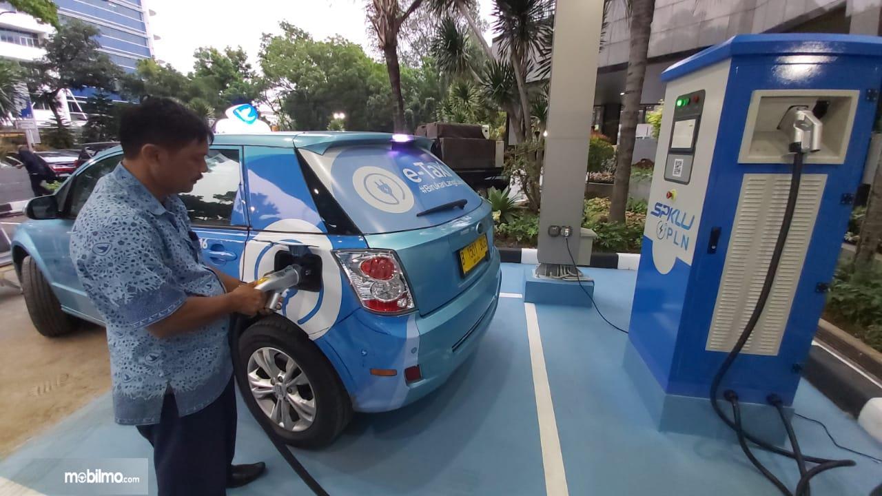 Foto seorang pengemudi taksi listrik Blue Bird mencoba sarana pengisian daya listrik milik PLN