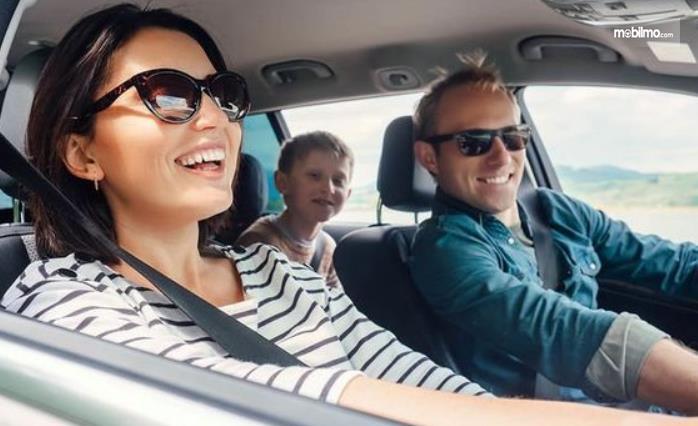 Gambar ini menunjukkan 3 orang sedang berada di dalam mobil