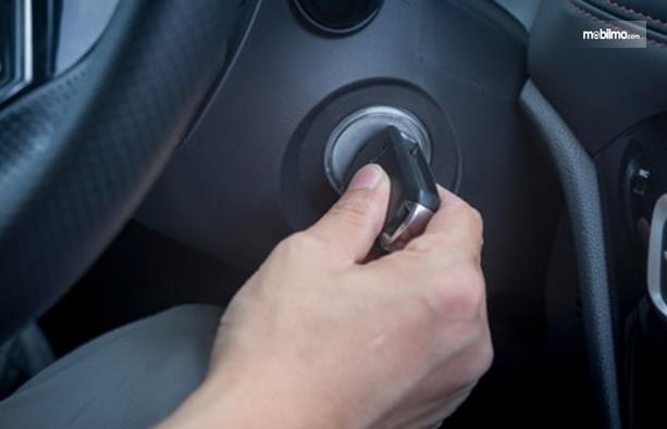 Gambar ini menunjukkan sebuah tangan memegang kunci dan ingin menyalakan mesin mobil