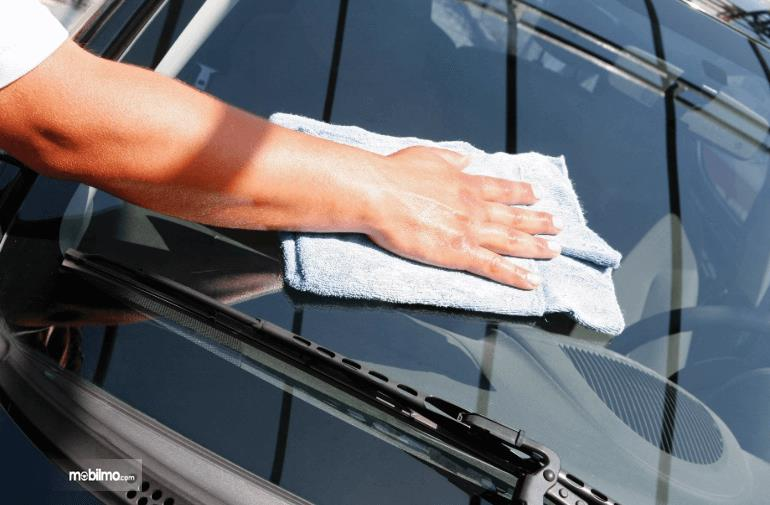 Gambar ini menunjukkan sebuah tangan memegang kain sedang mengelap kap mobil