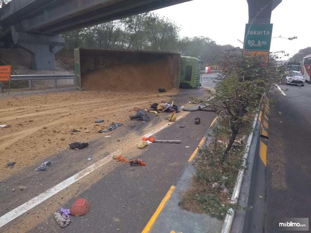 Foto truk pengangkut tanah terbalik di Jalan Tol Cipularang