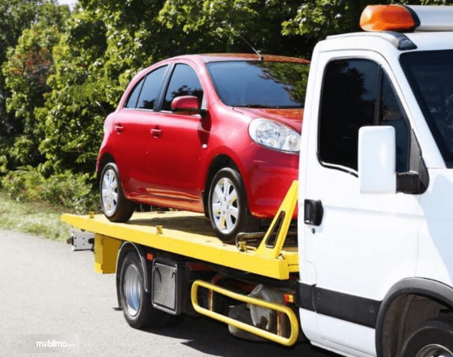 Gambar ini menunjukkan mobil warna merah sedang dinaikkan pada mobil towing