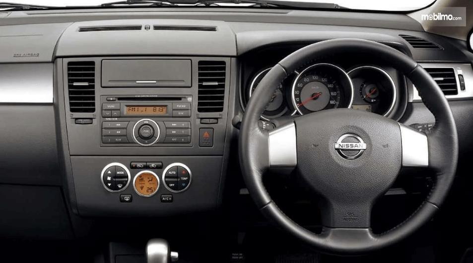 Gambar ini menunjukkan dashboard dan kemudi mobil Nissan Latio 2005