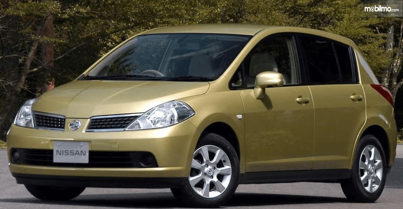 Gambar ini menunjukkan mobil Nissan Latio 2005 tampak bagian depan dan samping kiri
