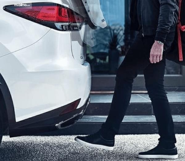 Gambar ini menunjukkan kaki mobil di tempatkan di belakang mobil untuk buka pintu bagasi