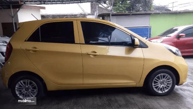 Gambar ini menunjukkan bagian samping mobil KIA Morning 1.0 2014 warna kuning