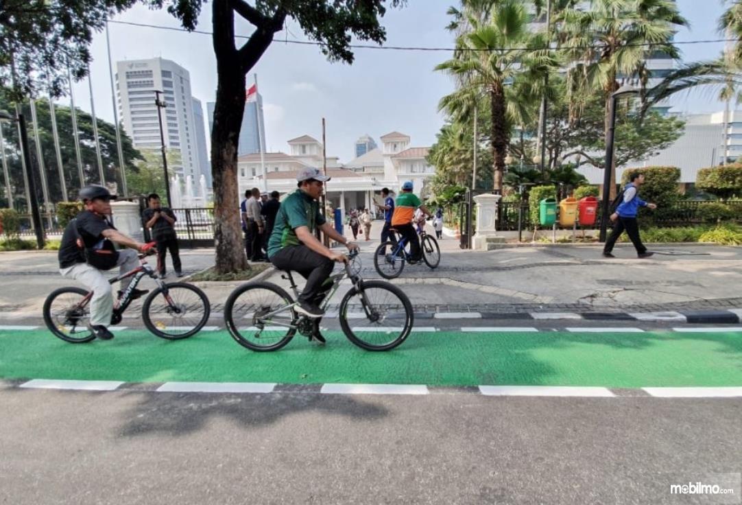 Gambar ini menunjukkan 2 sepeda melintasi jalur sepeda