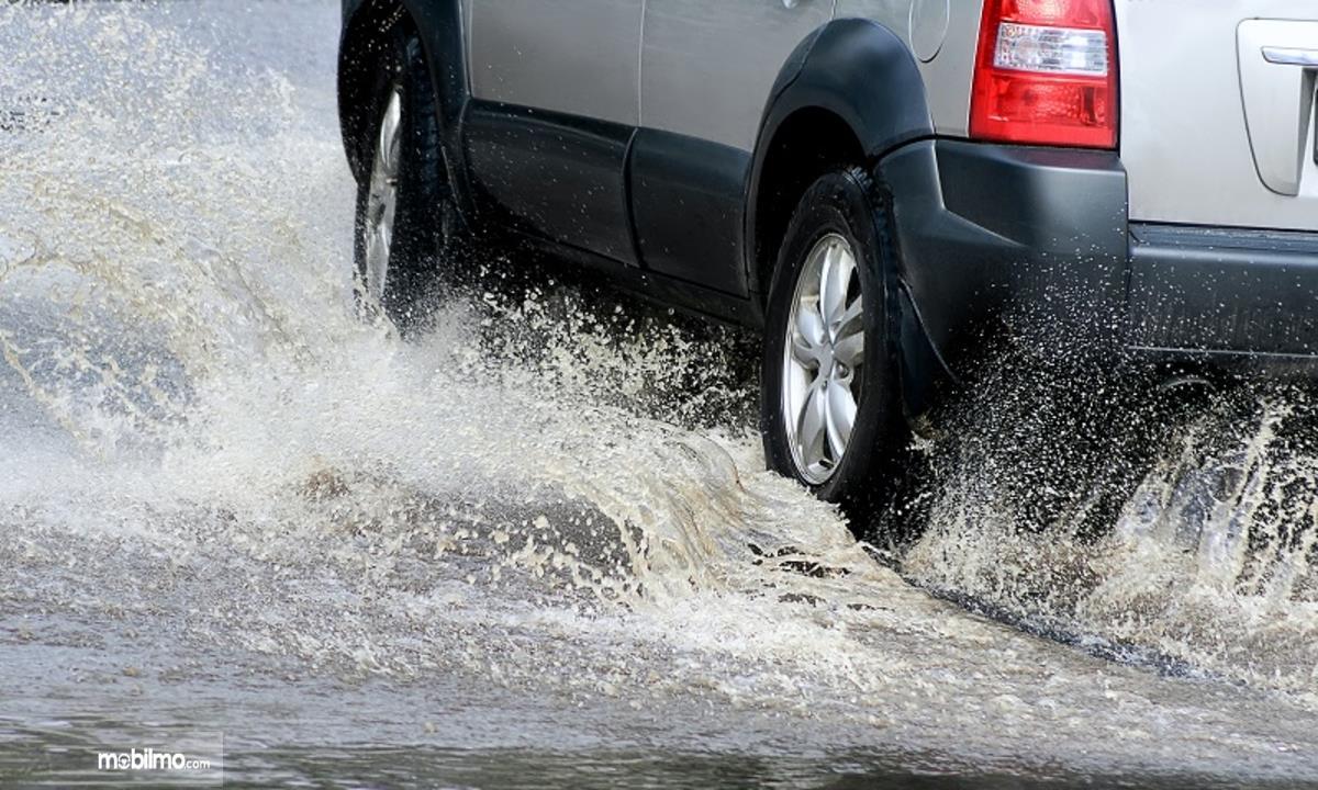 Foto mobil berjalan di genangan air