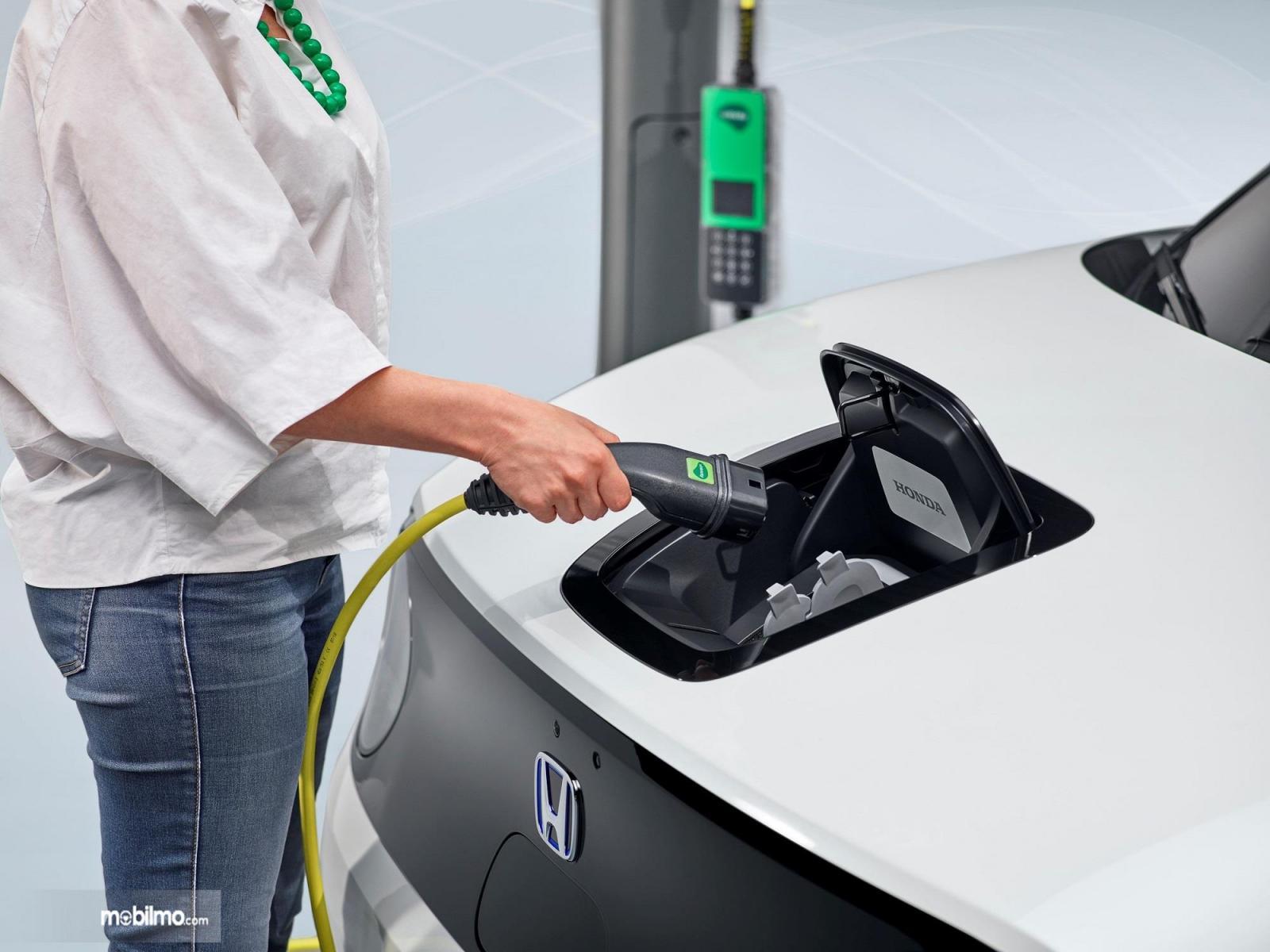 Foto seorang sedang mengisi  dengan Honda e charging port
