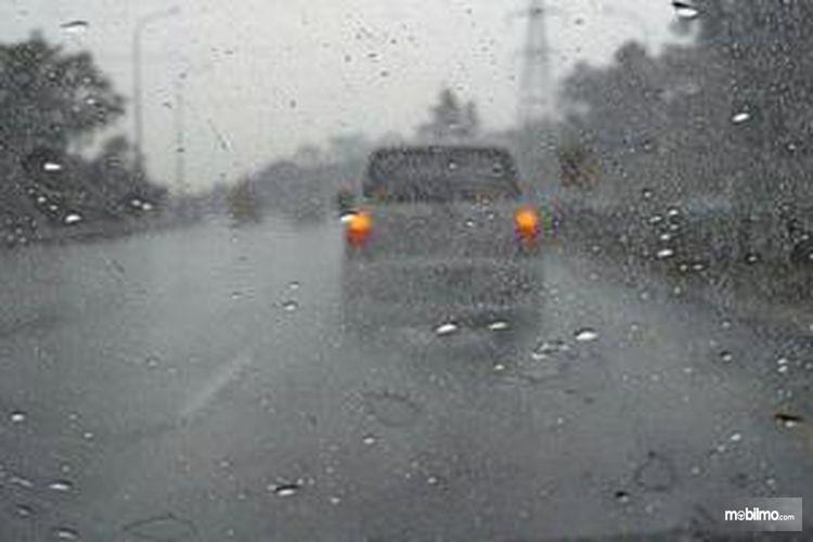Foto sebuah mobil sedang mengemudi saat hujan