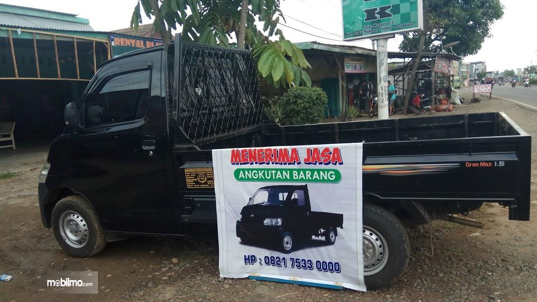 Foto mobil dengan banner jasa angkutan barang