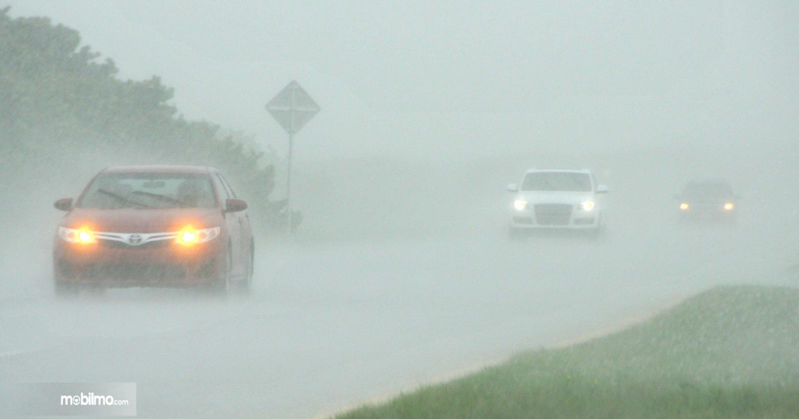 Foto mobil-mobil melintas di jalanan dengan lampu menyala saat hujan deras