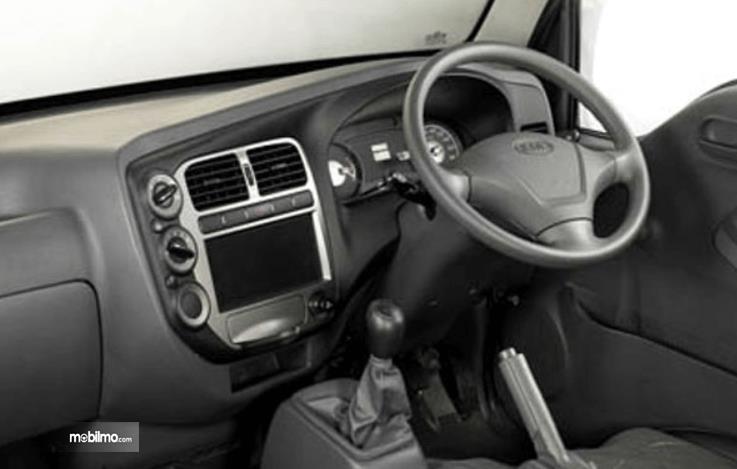 Gambar ini menunjukkan dashboard  dan kemudi mobil KIA Travello 2006