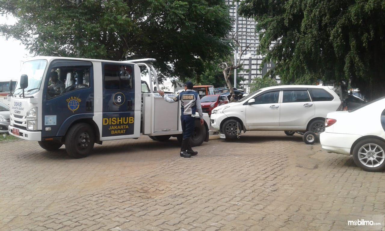 Foto petugas sedang menderek mobil yang melanggar aturan parkir