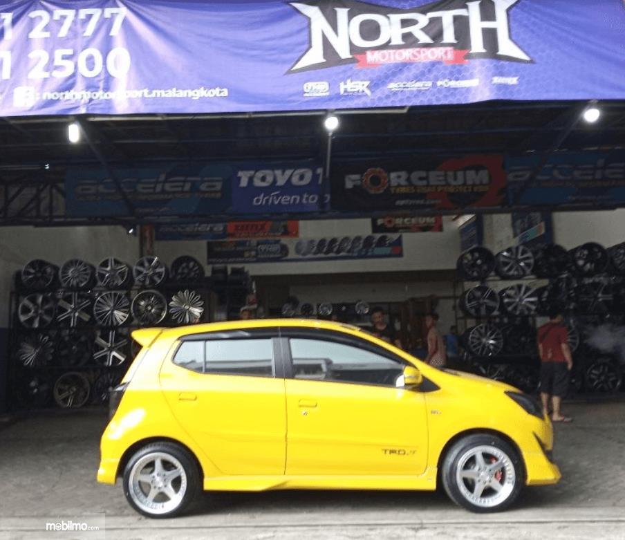 Gambar ini menunjukkan mobil warna kuning di depan bengkel modifikasi