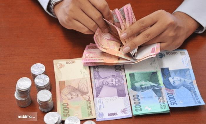 Gambar ini menunjukkan sebuah tangan memegang uang 100 ribuan dan banyak lagi didepannya