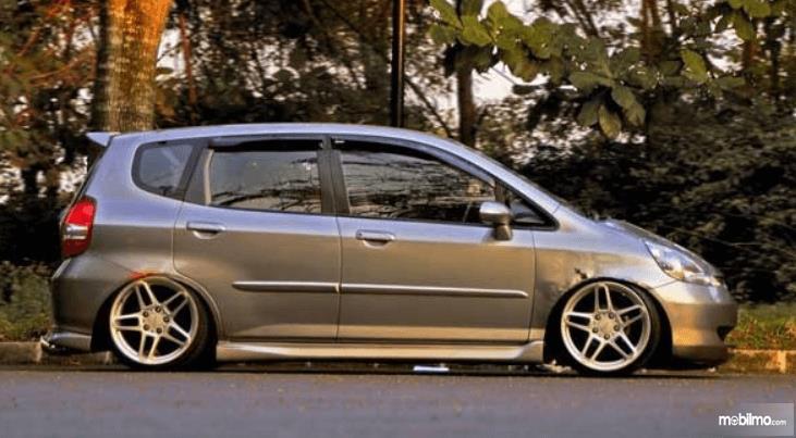 Gambar ini menunjukkan sebuah mobil tampak samping terlihat ceper