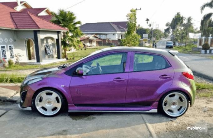 Gambar ini menunjukkan mobil modifikasi warna ungu