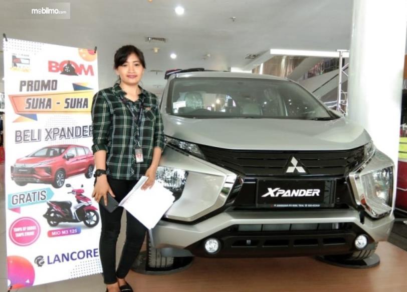 Gambar ini menunjukkan seorang wanita berdiri disamping mobil Mitsubishi Xpander