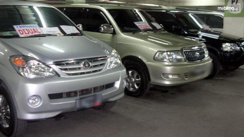 Gambar ini menunjukkan beberap mobil bekas sedang dijual;