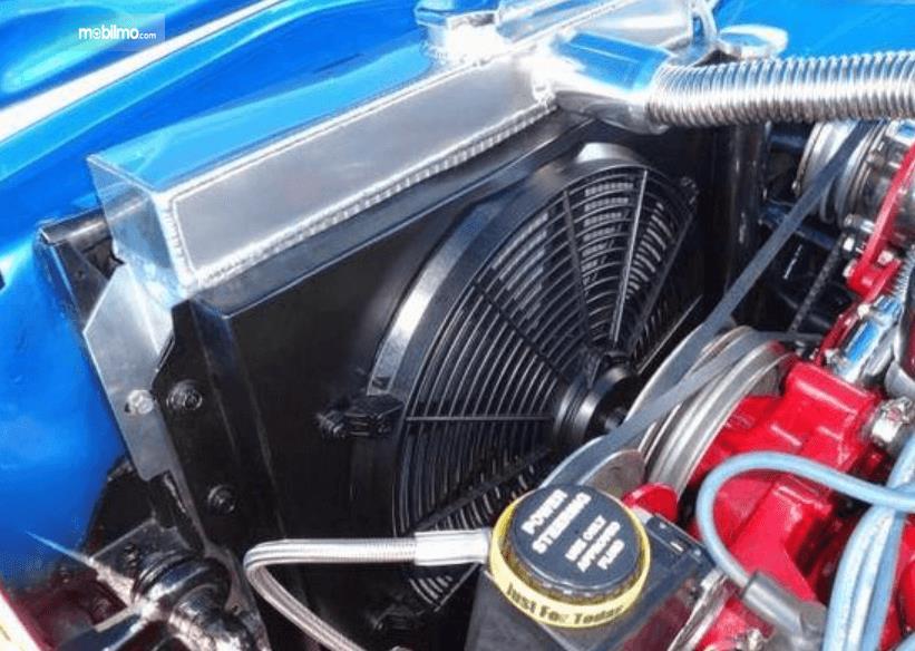 Gambar ini menunjukkan komponen pada mesin mobil dan terdapat kipas radiator