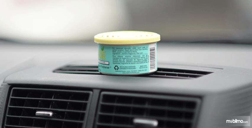 Gambar ini menunjukkan parfum mobil diletakkan di atas dashboard