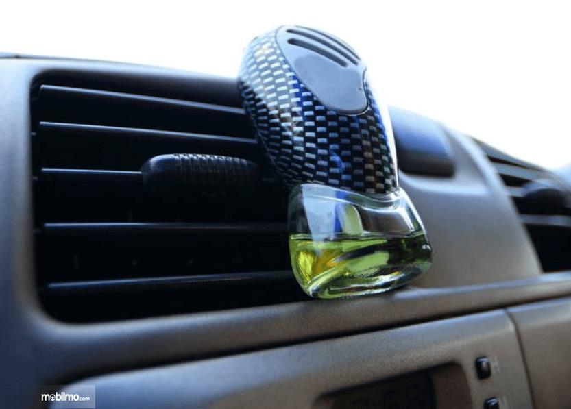 Gambar ini menunjukkan parfum mobil ditempatkan pada kisi-kisi AC