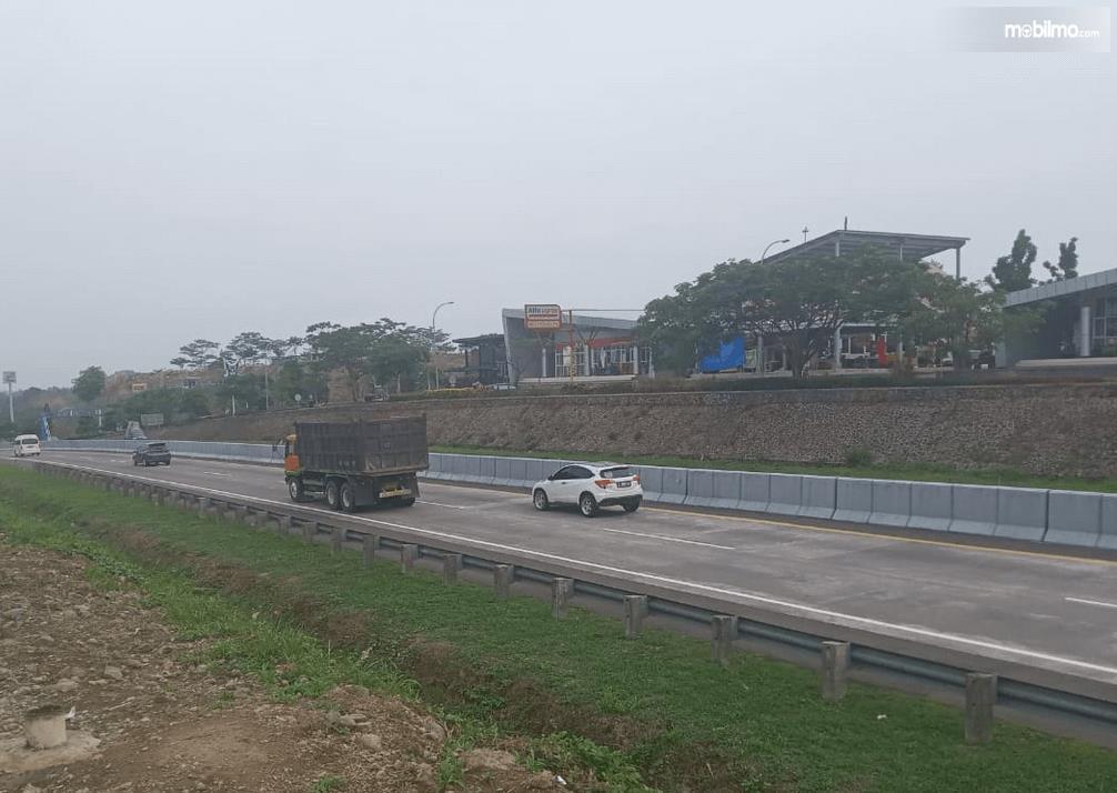 Gambar ini menunjukkan beberapa mobil melaju di jalan tol