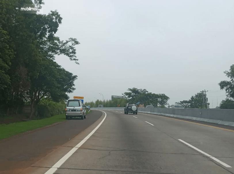 Gambar ini menunjukkan jalan tol dan terdapat 2 mobil di depannya