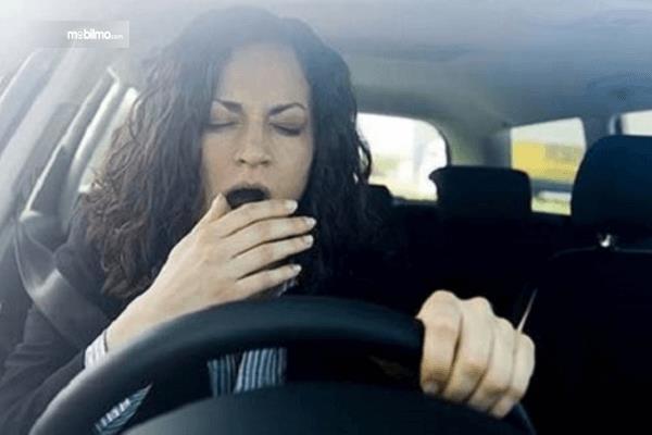 Gambar ini menunjukkan seorang wanita mengemudi mobil sambil menguap