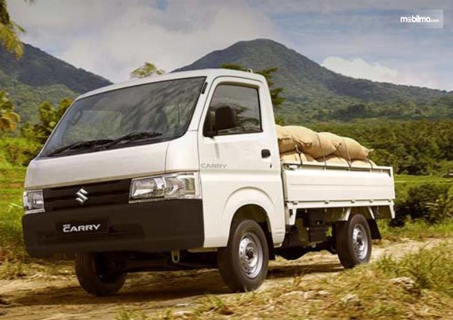 Gambar ini menunjukkan mobil Suzuki Carry membawa barang bawaan
