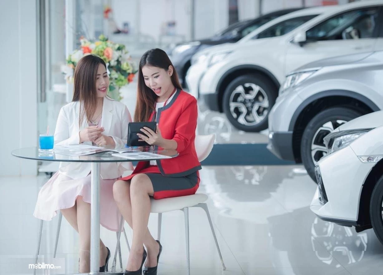 Foto menunjukkan dua orang sedang membaca brosur mobil baru