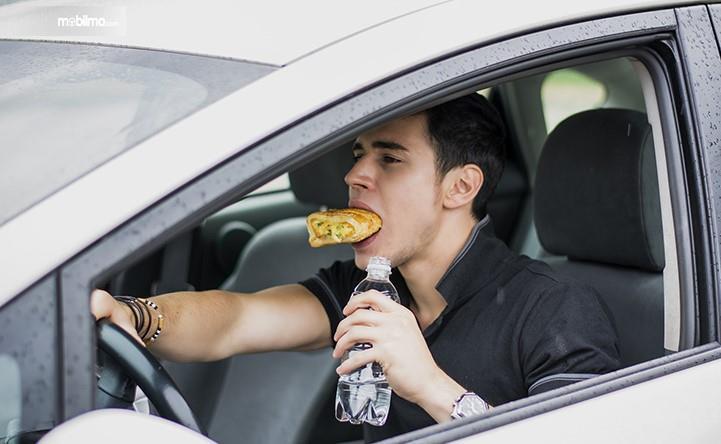 Foto menunjukkan seorang sedang mengemudi sambil makan