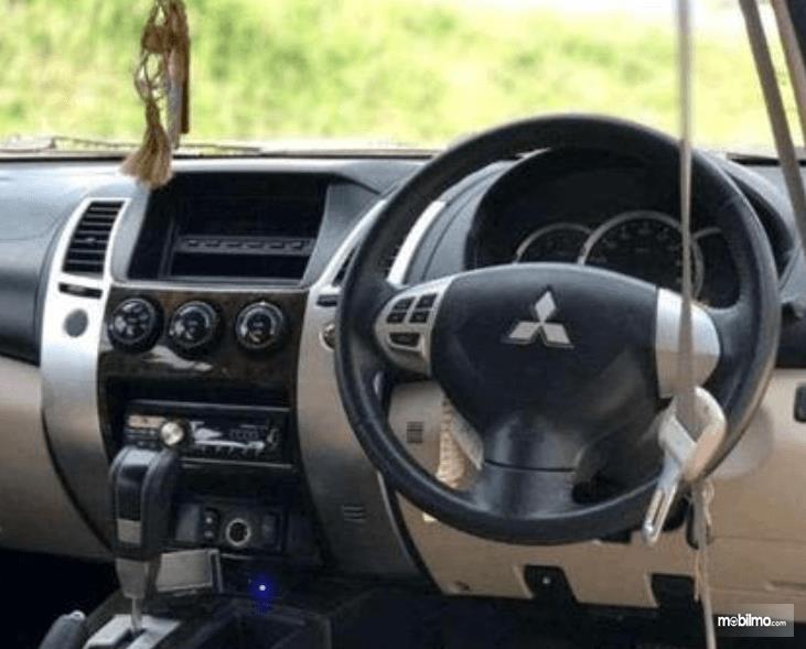 Gambar ini menunjukkan kemudi dan head unit Mitsubishi Pajero Sport 2009