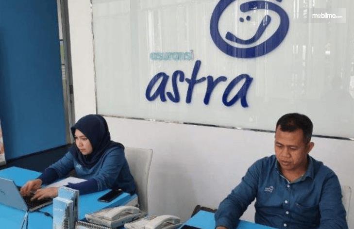 Gambar ini menunjukkan 2 pegawai  asuransi astra sedang duduk