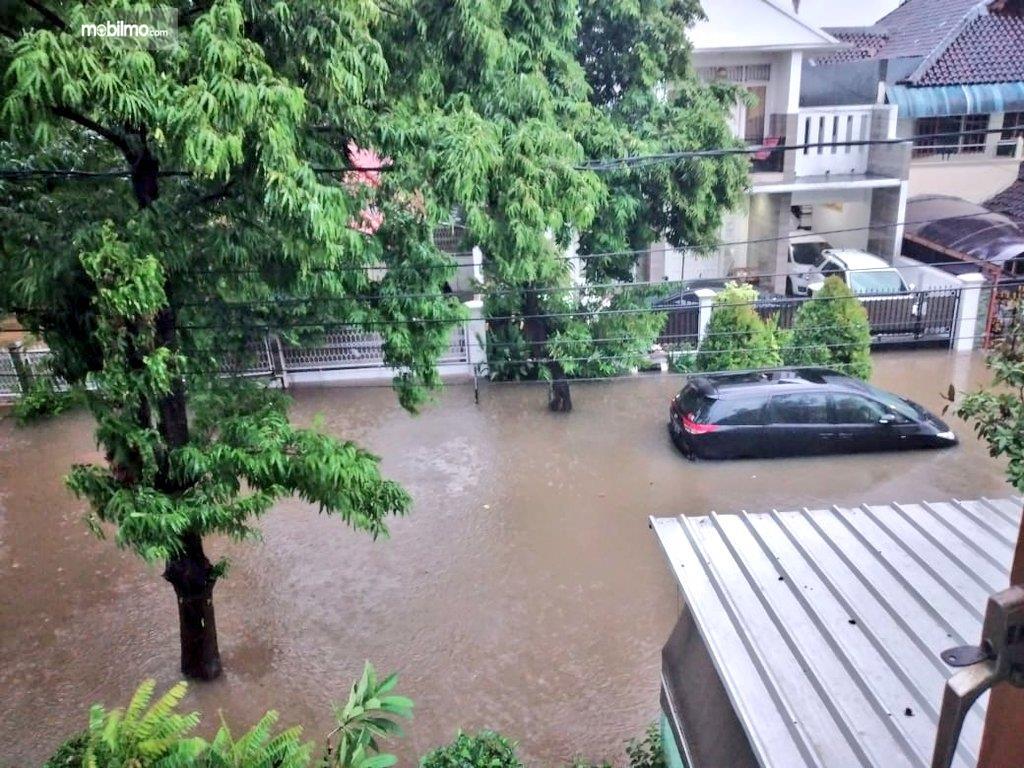 Foto menunjukkan Mobil terendam banjir hingga setengah bodi