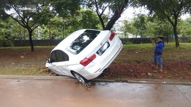 Foto menunjukkan Mobil BMW tersangkut pohon