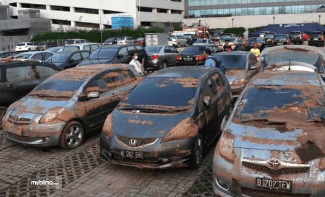 Foto menunjukkan mobil-mobil berkarat di parkir di tanah lapang