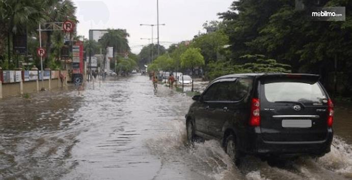 Gambar ini menunjukkan sebuah mobil warna hitam melintasi banjir