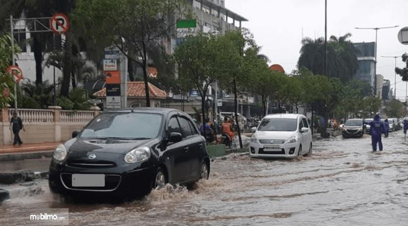 Gambar ini menunjukkan beberapa mobil melewati jalanan yang terkena banjir