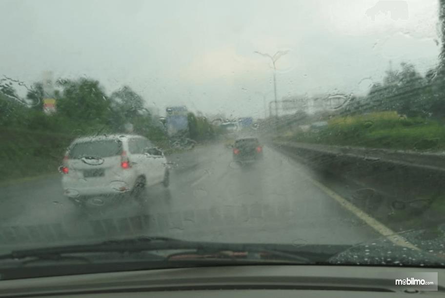 Gambar ini menunjukkan beberapa mobil sedang melintasi jalanan dalam kondisi hujan