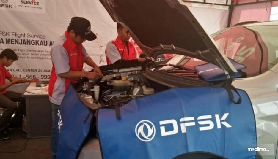 Gmbar ini menunjukknan sebuah mobil sedang diperbaiki  oleh mekanik DFSK